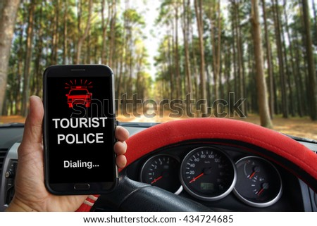 """""""TOURIST POLICE Dialing"""" showing on the smartphone inside of a pickup truck. - stock photo"""