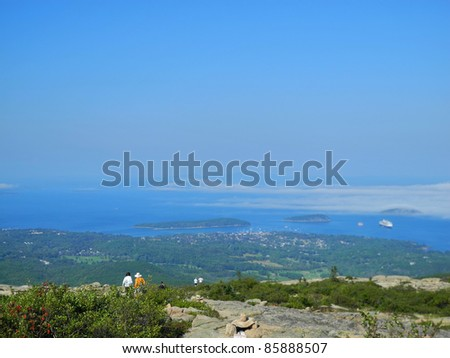 Tourists absorb the scenic view from Cadillac Mountain in Acadia National Park in Maine, with pink granite boulders, lichen and lush shrubbery, and glistening water below. - stock photo