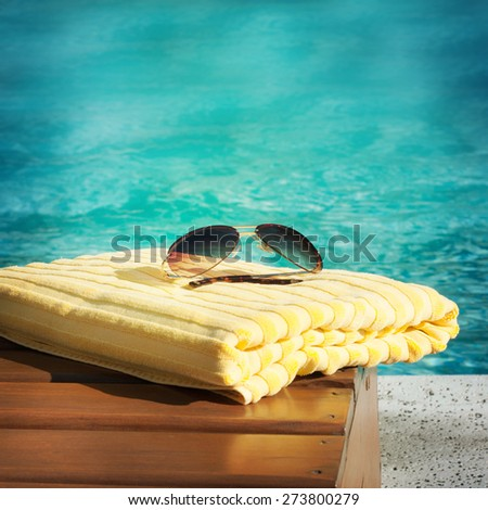 towel lying on a lounger beside the swimming pool - stock photo