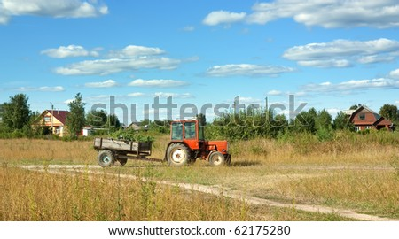 Tractor on meadow grass in summer day