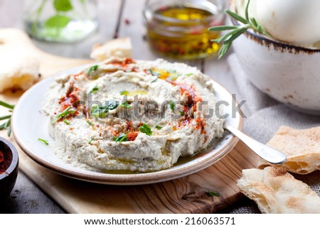 Traditional arabian eggplant dip baba ganoush with herbs and smoked paprika on a wooden background - stock photo
