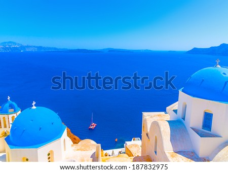 2 Traditional old churches with blue colored domes in Oia the most beautiful village of Santorini island in Greece - stock photo
