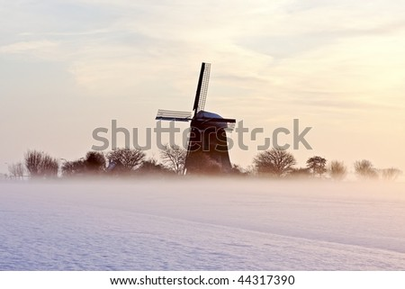Traditional windmill at twilight with fog and snow in winter in the Netherlands - stock photo