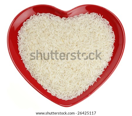 Traditionally Indian basmati Rice in red heart shaped plate, isolated over white - stock photo