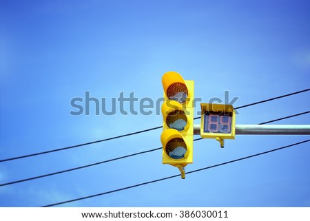 Traffic light at intersection with clear blue sky. - stock photo