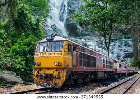 train passes through the mountain and cascade   landscape  - stock photo