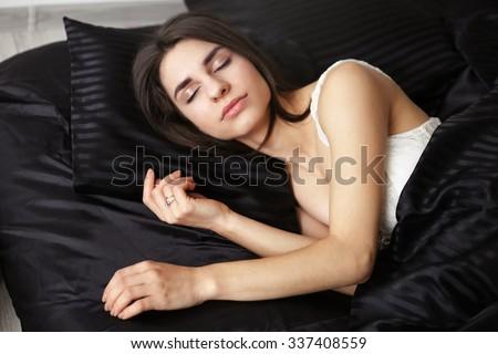 Tranquil sleeping girl. Brunette girl in bed. Girl with eyes closed. Young beautiful woman on the bed. Healthy sleep. Sweet sleep. Deep sleep. Orthopedic mattress. Sweet dreams. Selective focus. - stock photo