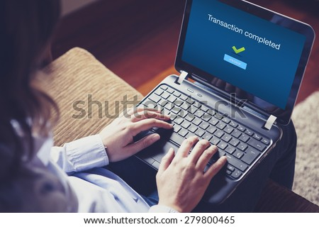 """Transaction completed"" on the screen. Hands over the keyboard on laptop. - stock photo"