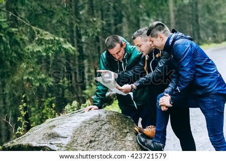 travelers looking to map in mountains - stock photo