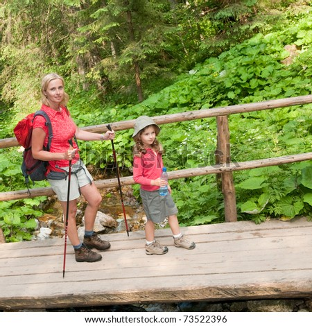 Trekking - little girl with mother on mountain trek - stock photo