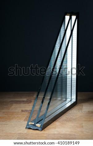 triple glazing, wooden base, black background - stock photo