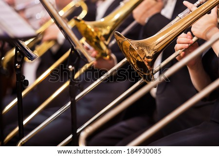 Trombones in the hands of musicians on stage