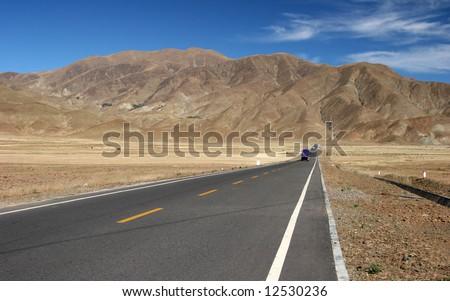 Truck driving on a highway near mountain range. Kagbeni, Annapurna trekking, Himalaya, Nepal - stock photo