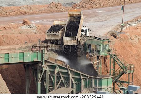 trucks dump coal to the conveyor at the lignite opencast mining - stock photo