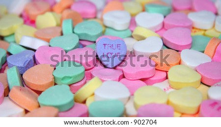 """""""True Love"""" candy heart surrounded by other candy hearts. - stock photo"""