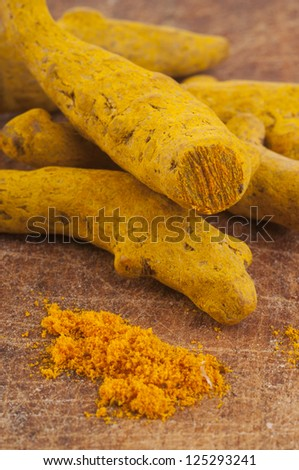 Turmeric root on wooden background - stock photo
