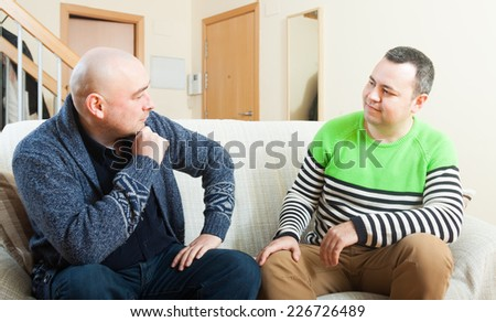 Two adult men discussing something at home - stock photo