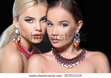 Two beautiful women with necklace and earrings. Jewelry and beauty - stock photo