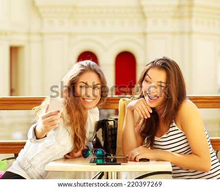 Two beautiful young women making selfie and grimacing - stock photo