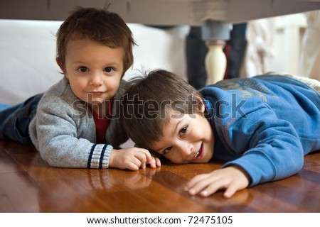 Two brothers playing on the floor. - stock photo