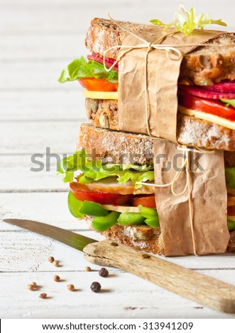 Two delicious sandwiches wrapped in papper and tied with kitchen twine. Selective focus. - stock photo