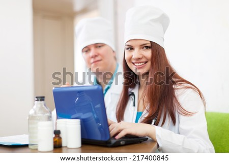 two doctors with laptop in clinic interior - stock photo