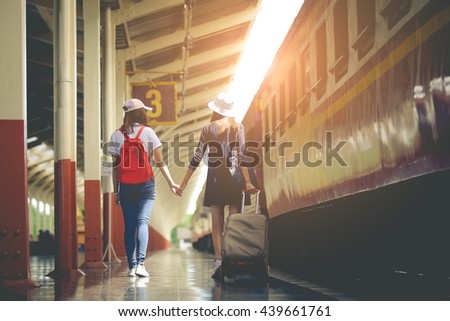 Two female tourists walking on the station platform.