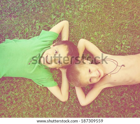 two friends laying in the grass done with a retro vintage instagram filter