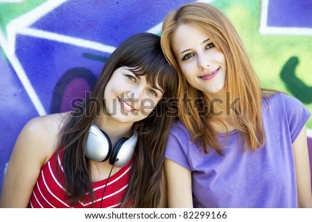 Two girlfriends near graffiti wall. - stock photo