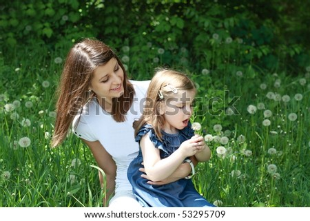 Two girls play on the glade with dandelions