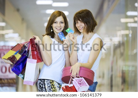 Two girls with packages show credit cards - stock photo