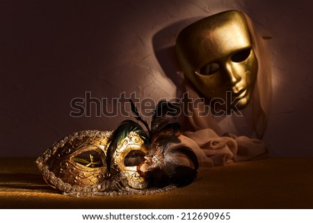 Two golden Venetian masks , focus on foreground