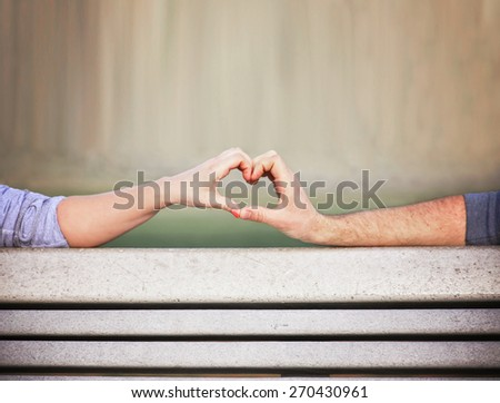 two people making a heart shape with their hands on a bench (shallow depth of field on the thumbs)  - stock photo