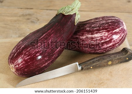 two purple and white aubergines or eggplants on a wooden board                              - stock photo