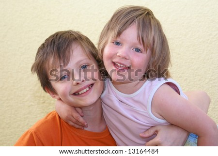 Two siblings embrace each other and laughing happily.  Isolated.