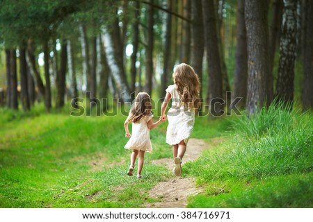 Two sisters run through the forest  holding hands. Summer sunny day and girls in light dresses. Beautiful long hair in a child.