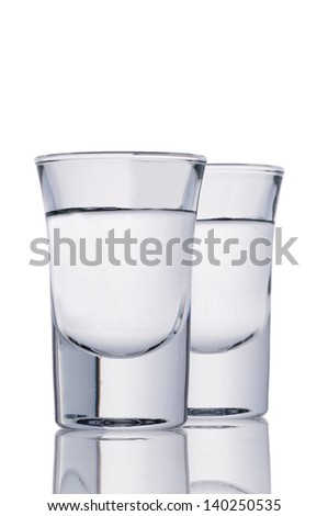 Two small shot glasses filled with alcohol isolated on white.Path - stock photo
