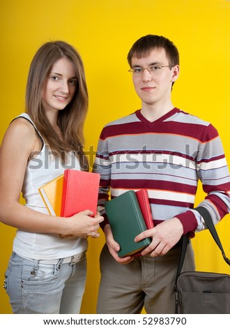 Two students with books  over a yellow background.