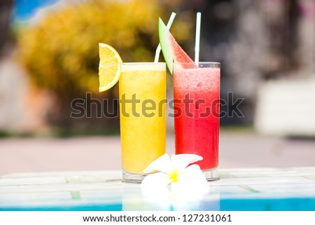 two tropical fruit alcohol cocktails near pool - stock photo