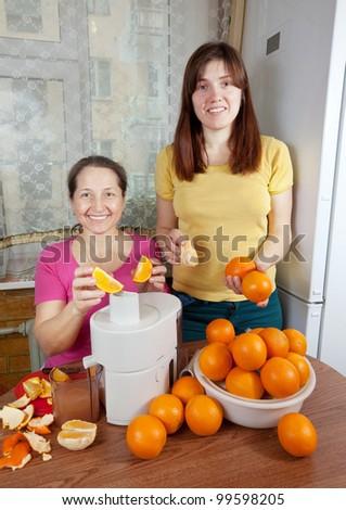 Two women  making fresh orange juice in home kitchen - stock photo