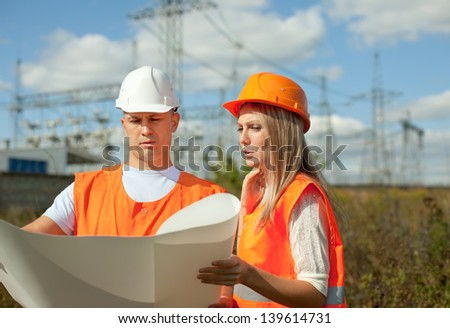 two workers wearing protective helmet works at electrical power station. - stock photo
