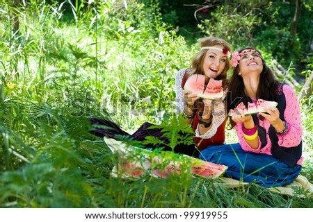 Two young beautiful girls eat a water-melon on a lawn - stock photo