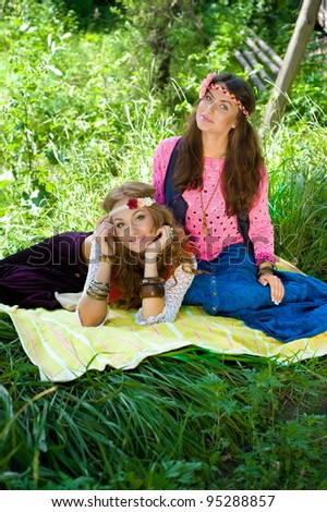 Two young beautiful girls   hippie have a rest on a lawn - stock photo