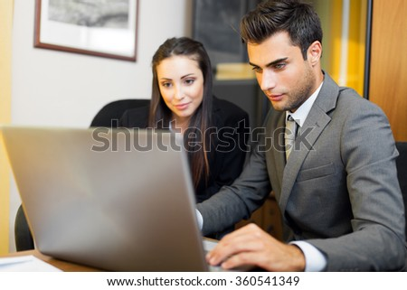 Two young business partners discussing plans or ideas at meeting  - stock photo
