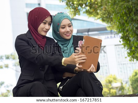Two young business woman with using tablet touchscreen