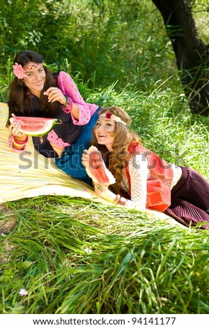 Two young women on a picnic in summer park hippie style series - stock photo