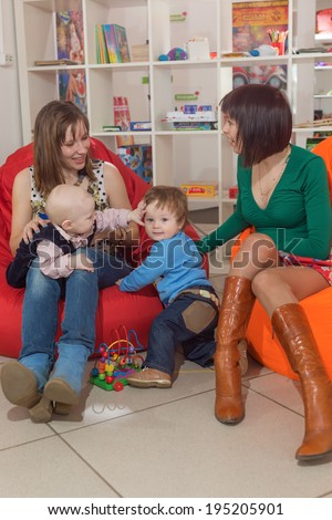 Two young women talk, children play - stock photo