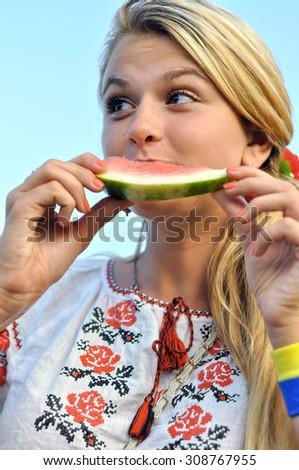 ukrainian teenage girl eating watermelon outdoor - stock photo