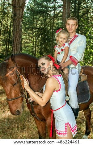 Ukrainians mom and dad daughter ride in the woods on horseback