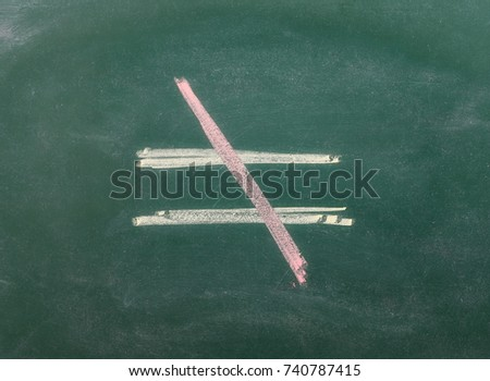 Unequal symbol, sign on chalkboard, blackboard texture